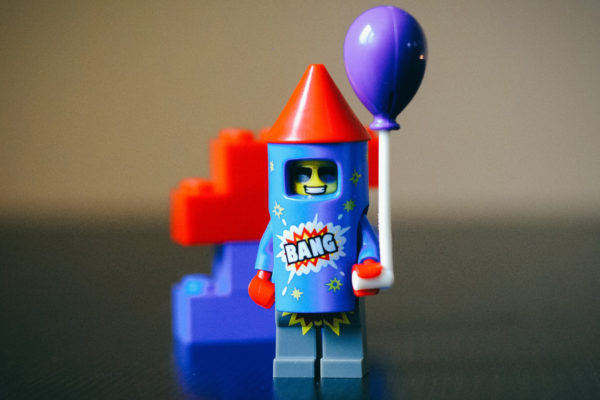 Smiling lego man dressed as a firework holding a balloon.