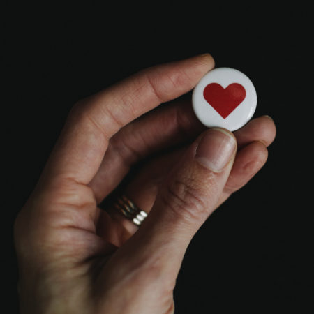 Close up of a hand holding a badge with a heart shape on.